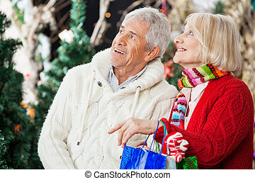 Happy Couple Shopping At Christmas Store - Happy senior...