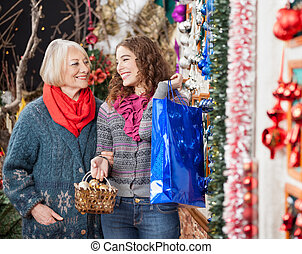 Mother And Daughter Shopping In Christmas Store - Happy...