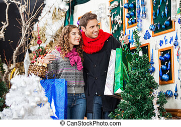 Young Couple Shopping At Christmas Store - Happy young...