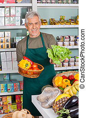 Senior Salesman Selling Vegetables In Supermarket - Portrait...