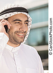 Arab businessman on the phone Cheerful Arab businessman...