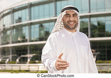 Good deal! Cheerful Arab businessman stretching out his hand...