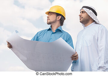 Arab businessman and builder. Low angle view of Arab...