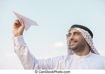 Arab businessman with paper airplane Cheerful Arab...