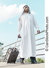 Business trip Full length of Arab businessman with suitcase