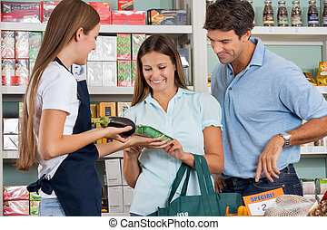 Saleswoman Assisting Couple In Buying Groceries - Saleswoman...
