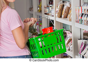 Midsection Of Woman Carrying Shopping Basket - Mid section...