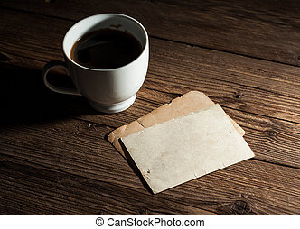 White cup of coffee and old paper photo frame on wood...