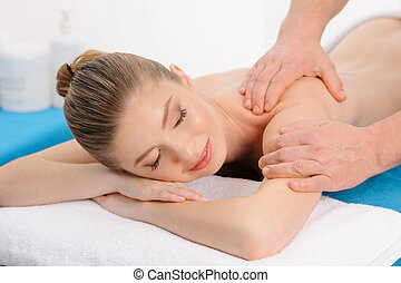 Enjoying in massage - Cheerful naked young woman lying on...
