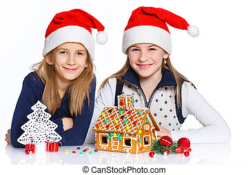 Girls in Santa's hat with gingerbread house - Christmas...