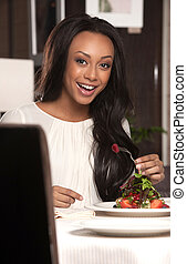 Woman at the restaurant. Beautiful African descent woman eating at the restaurant and smiling