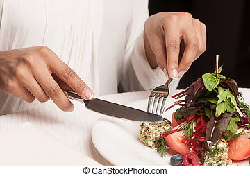 Woman at the restaurant. Cropped image of woman eating at...