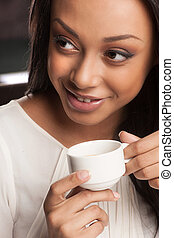 Beauty drinking coffee. Portrait of beautiful African descent women drinking coffee and looking away
