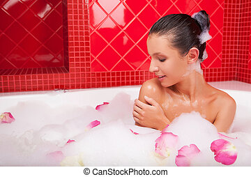 Beauty in bath Attractive young woman lying in bubble bath...