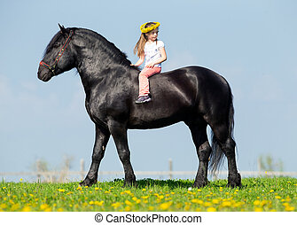 Child and big black horse at spring - Child riding a big...
