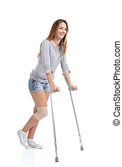 Beautiful woman smiling and hobbling with crutches isolated...