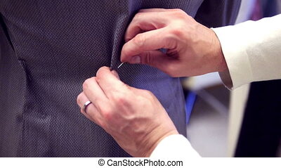Hands tailor a suit at fashion shoo