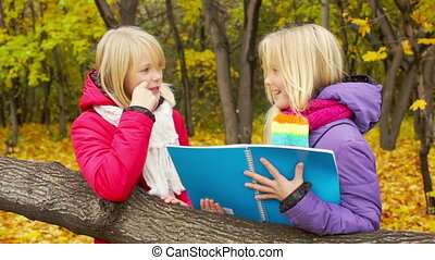 Homework Outdoors - Twin schoolgirls discussing homework...