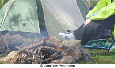 People Camping - Female backpacker sitting by campfire in...