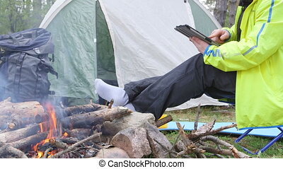 Female camper using digital tablet by campfire in the woods
