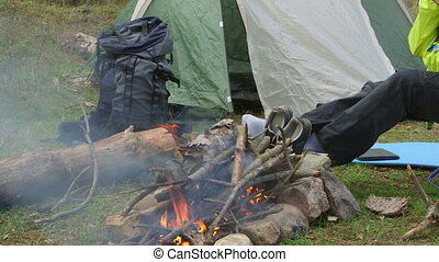 Woman Camping - Woman backpacker sitting by campfire at...