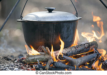 Cooking on campfire - Camping kettle over burning campfire