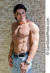 Muscular young bodybuilder shirtless outdoors in jeans,...