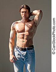 Handsome muscular man shirtless wearing jeans with hand...