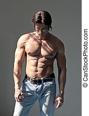 Handsome muscular man shirtless on grey background -...