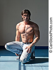 Attractive muscleman kneeling shirtless on grey background...