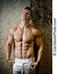 Attractive muscleman against rough wall - Handsome muscular...