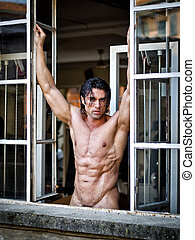 Handsome muscular man naked looking in camera on window...
