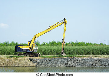 Excavator dredging the canal - Yellow Backhoe dredging the...