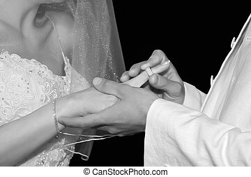 Wedding ring - Close-up groom puts wedding ring on brides...