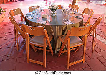 table setting for a wedding in colored lighting - table...