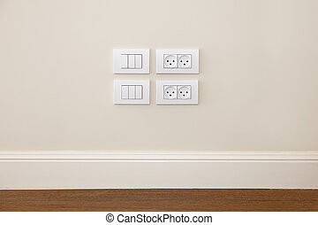 Power outlet and light switch on the wall - Empty wall with...