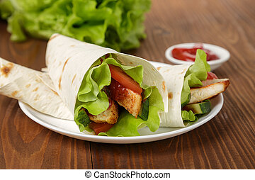 wheat tortilla with chicken and vegetables on plate on...