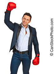 Successful business man raising hand in boxing gloves...