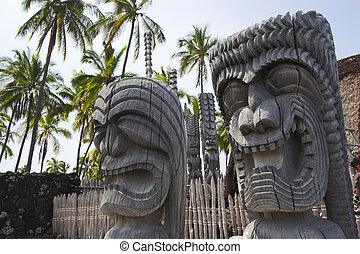 Wooden idols and temple - Wooden statues of idols standing...
