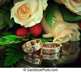 Golden wedding rings with bouquet. Focus on the rings