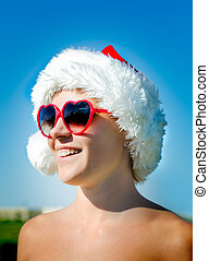 Santa girl wearing heart shaped sunglasses with outstretched...