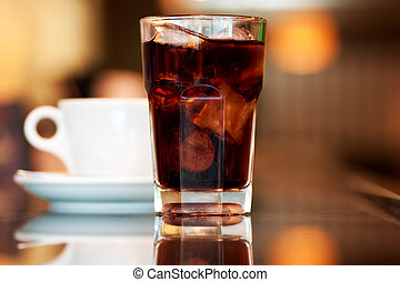 Cola and coffee - A glass of cola or soda with ice cubes and...