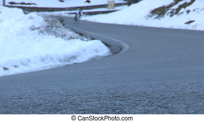 Cyclist going downhill on snowy road