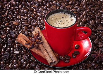 Coffee in a red cup with cinnamon and anise stars.