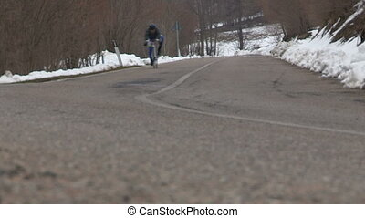 Cyclist going downhill on the road between snowy woods