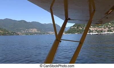 Seaplane sailing on Como lake, preparing for take off