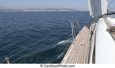 Left side of sailing boat navigating with open sails in the...