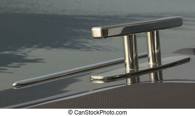 Chrome bitt on luxury boat, with water behind