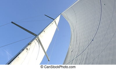 Open sails of sailing boat navigating in the sea