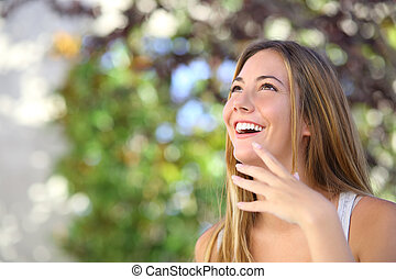 Beautiful woman laughing and looking above with a green...